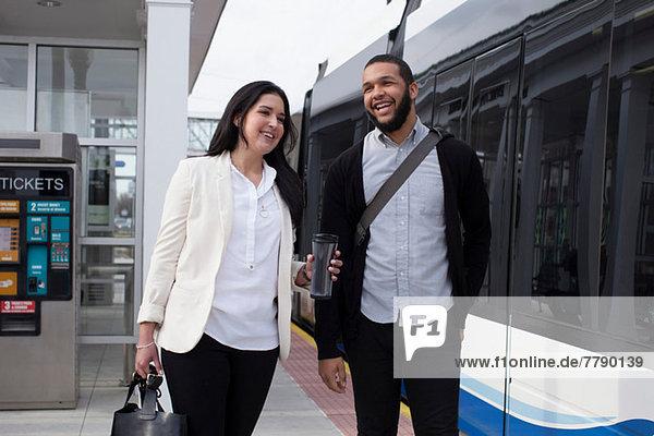 Junges Paar auf dem Bahnsteig mit leichtem Zug