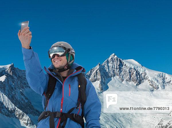 Junger Mann fotografiert sich selbst auf dem Smartphone in den Bergen