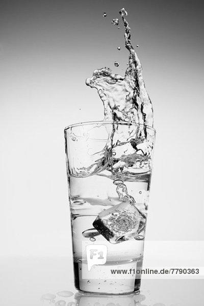Eiswürfel  der in ein Glas Wasser fällt.