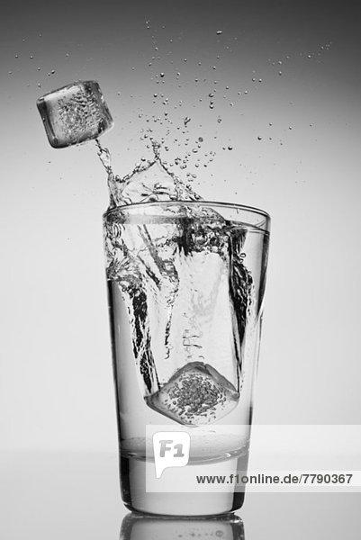 Eiswürfel  die in ein Glas Wasser fallen