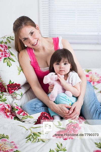 Mutter und Kleinkind auf dem Bett sitzend