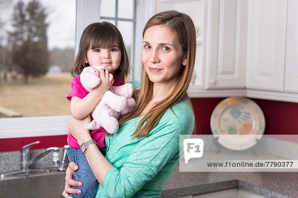 Porträt der Mutter mit Kleinkind-Tochter in der Küche