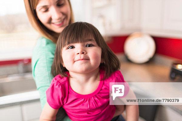 Mutter mit weiblicher Kleinkind-Tochter  um in die Kamera zu schauen.