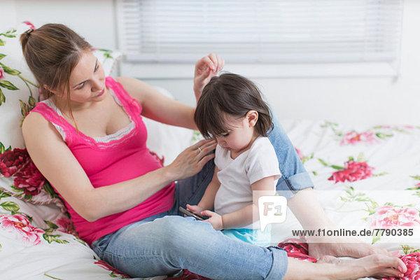 Schwangere Frau und Kleinkind Tochter auf dem Bett mit Blick auf Smartphone