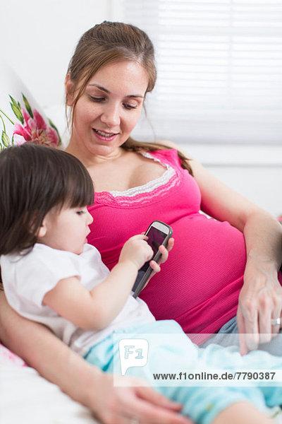 Schwangere Frau und Kleinkind Tochter beim Blick auf das Smartphone