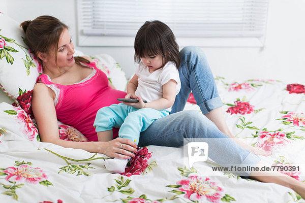 Porträt einer schwangeren Frau und einer Kleinkind-Tochter  die mit einem Smartphone auf dem Bett liegt.