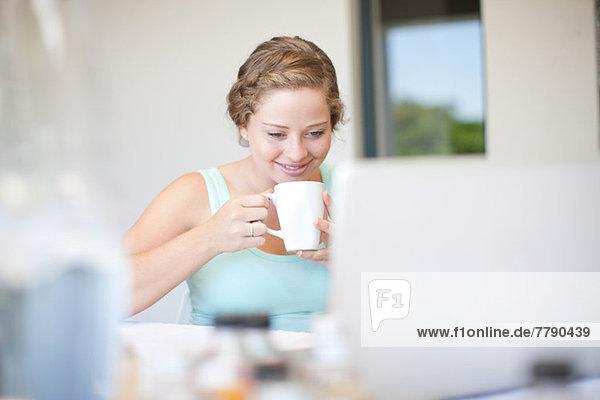 Junge Frau mit Laptop  die Tee trinkt