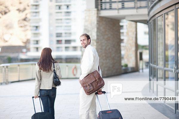 Junger Mann und junge Frau mit Koffern