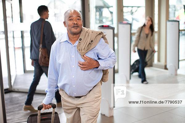 Senior im Flughafen mit Koffer