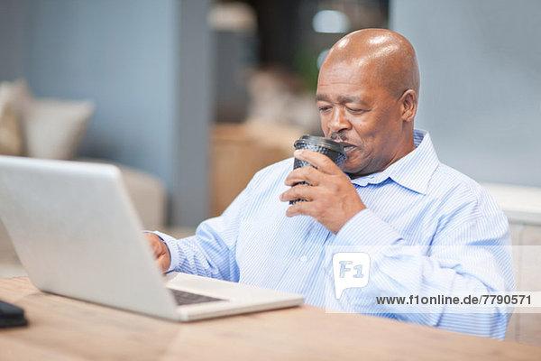 Businessman drinking coffee using laptop
