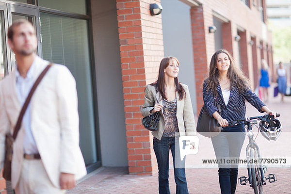 Junge Frauen auf dem Bürgersteig mit dem Fahrrad