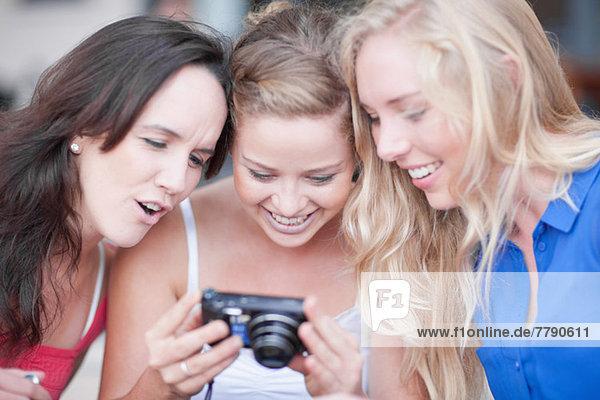 Drei junge Frauen beim Betrachten von Fotos