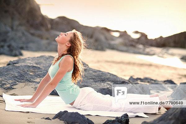 Junge Frau beim Yoga am Strand
