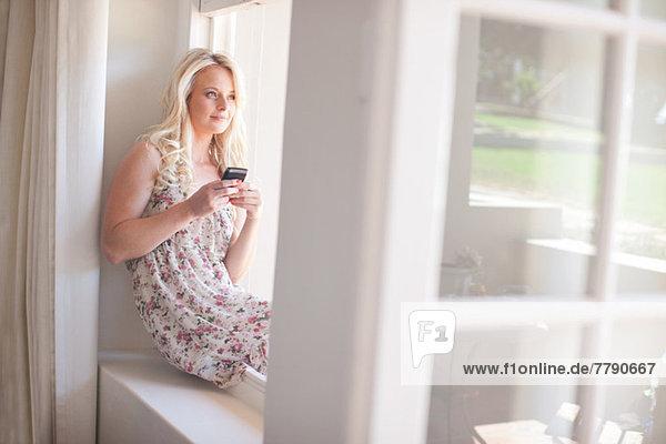 Junge Frau sitzt auf der Fensterbank und hält das Smartphone.