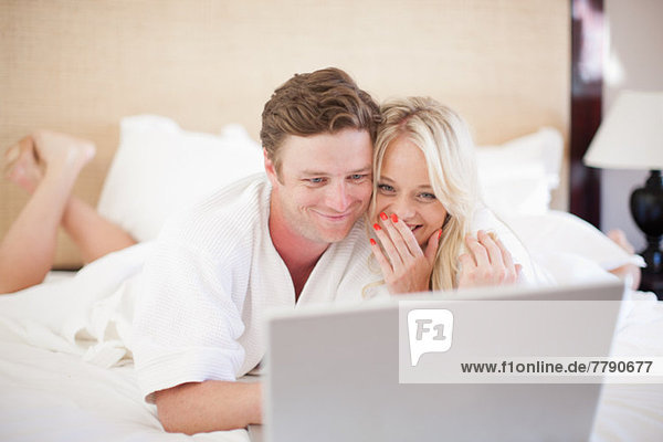 Young couple on bed using laptop