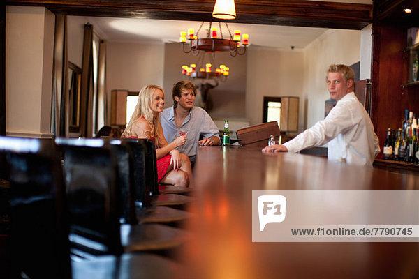 Kellner serviert junges Paar in der Bar