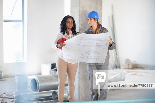 Architect and construction worker discussing blueprint