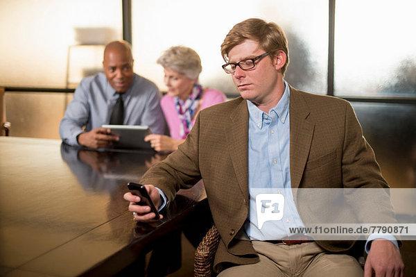 Junger Mann mit Handy und Kollegen im Hintergrund