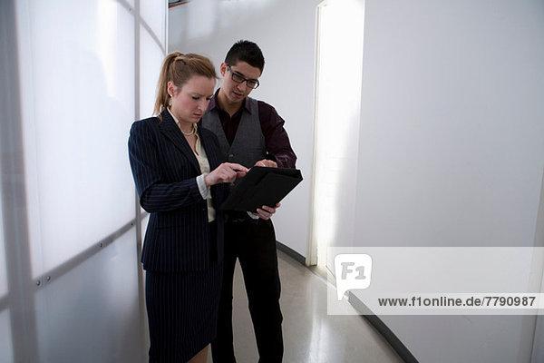 Junge Geschäftsleute im Flur mit digitalem Tablett