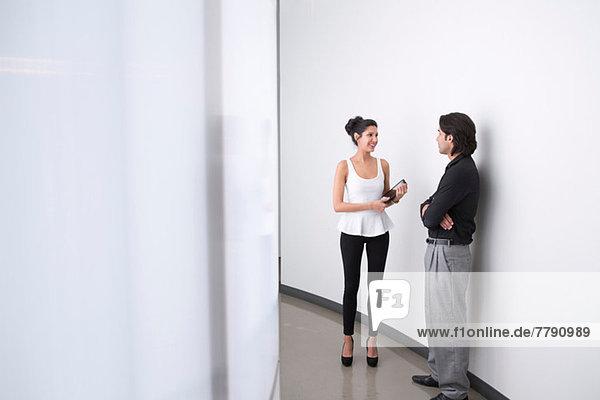 Junge Geschäftsleute im Flur im Gespräch