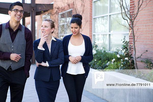 Drei junge Geschäftsleute außerhalb des Bürogebäudes