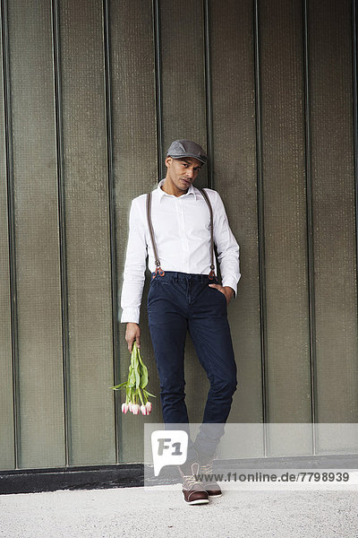 Man Leaning Against Wall Holding Flowers  Mannheim  Baden-Wurttemberg  Germany