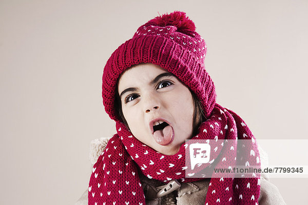Close-up Portrait of Girl Making Faces and wearing Hat and Scarf in Studio