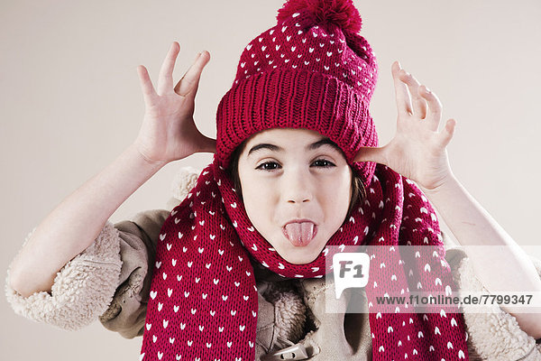 Portrait of Girl making faces wearing Hat and Scarf in Studio
