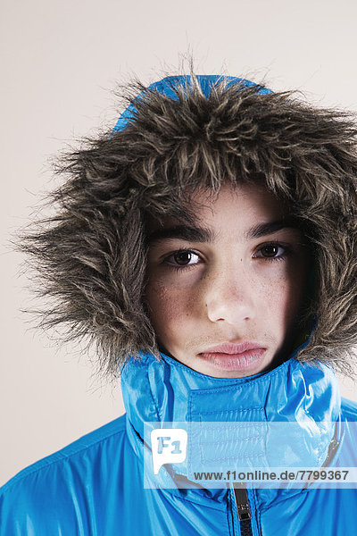 Portrait of Boy in Winter Jacket with Faux Fur Trimmed Hood in Studio