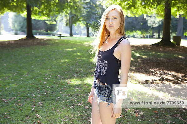 Portrait of young woman in park on a warm summer day in Portland  Oregon  USA