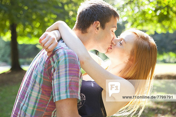 Young Couple Kissing in Park on a Summer Day  Portland  Oregon  USA