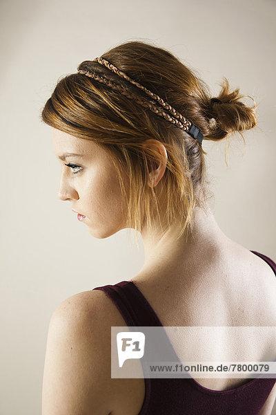 Profile  head and shoulders portrait of teenage girl in studio.