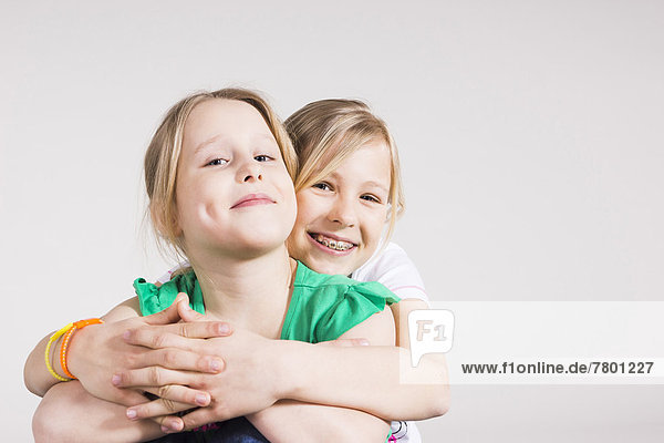 Portrait  umarmen  Schwester  Studioaufnahme  Mädchen