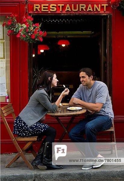 France  Paris  Young couple sitting in sidewalk cafe
