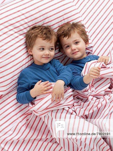 USA  Utah  Orem  Twin boys (2-3) wearing pajamas playing on bed