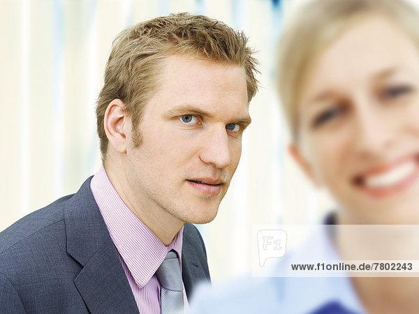 Geschäftsmann,  hinter lächelnder Geschäftsfrau