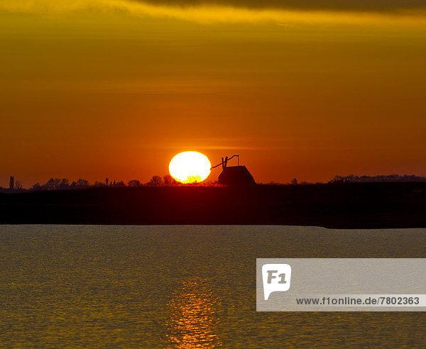 Sonnenaufgang mit Ziehbrunnen bei der Darscho-Lacke oder Warmsee