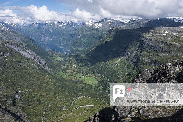 Tourist steht auf einem Felsen auf dem Berg Dalsnibba  1495m  hinten der Geirangerfjord