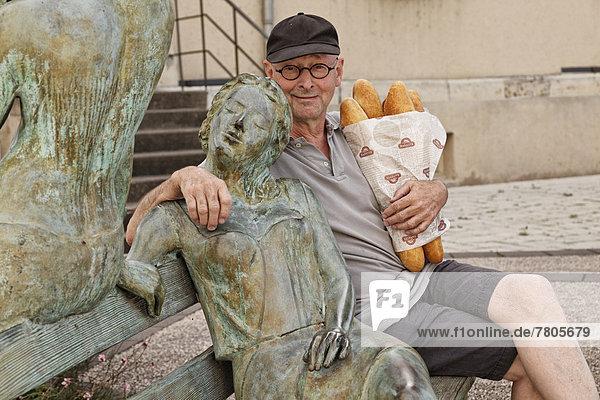 Mann mit Baguette-Einkauf sitzt neben Skulptur vor dem Rathaus