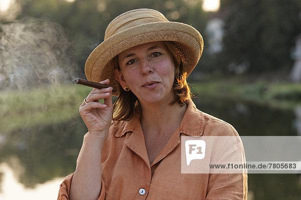 Frau raucht Zigarre  auf Hausboot auf dem Canal des Vosges  früher Canal de l?Est  Abendstimmung