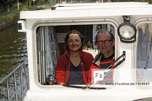 Frau und Mann am Steuer einer Penichette  Hausboot auf dem Canal des Vosges  früher Canal de l?Est