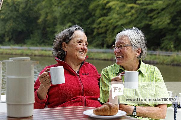 Zwei Urlauberinnen beim Frühstück auf der Heckterrasse einer Penichette  Hausboot auf dem Canal des Vosges  früher Canal de l?Est  bei PK 101