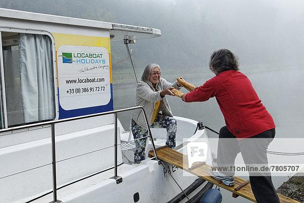 Baguette-Einkauf für das Frühstück  Hausboot auf dem Canal des Vosges  früher Canal de l?Est  im Hafen mit Morgennebel
