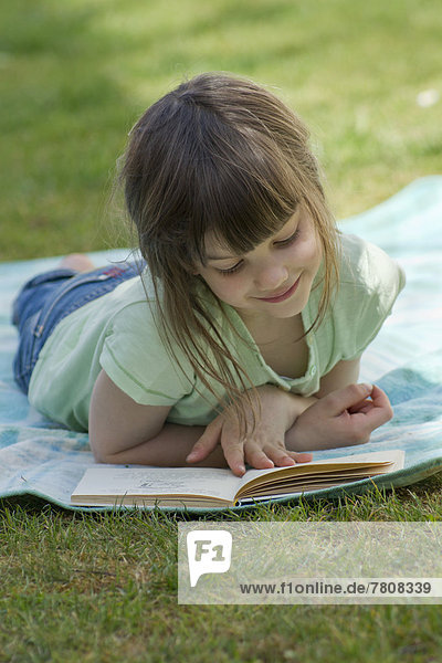 Girl lying and reading book  smiling