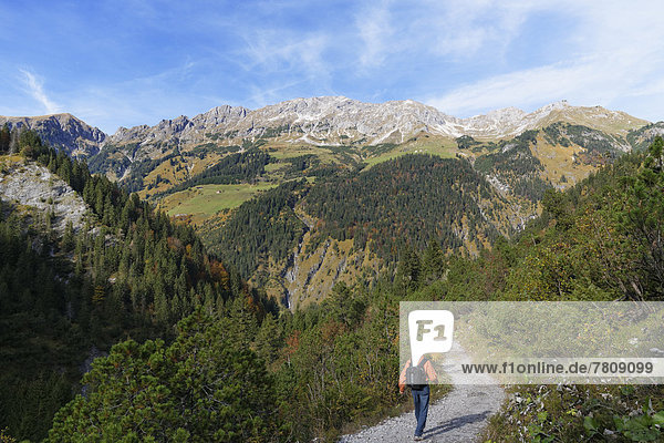 Austria  Vorarlberg  Man walking on single track with mountains in background
