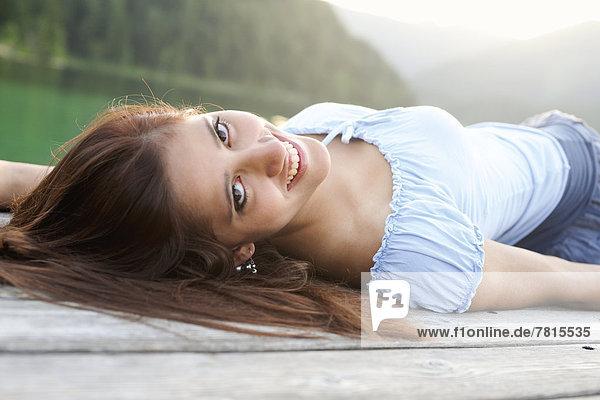 Junge Frau liegt auf Steg  im Sommer