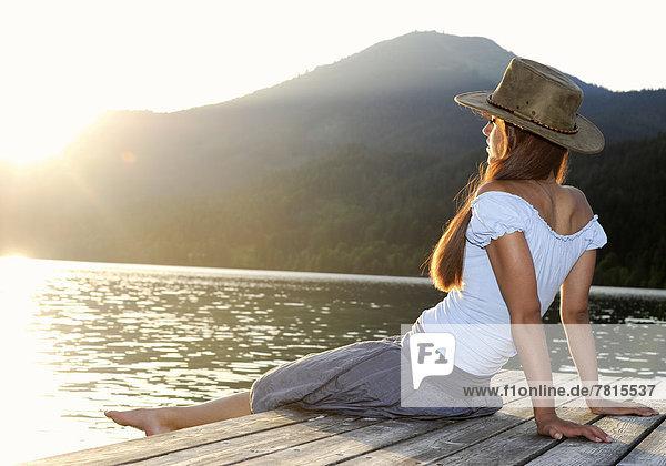 Junge Frau sitzt auf Steg  im Sommer