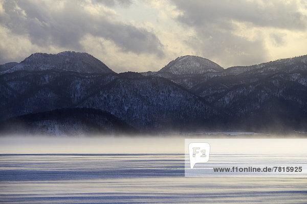 Nebelschwaden über dem zugefrorenen See Kussharo Lake