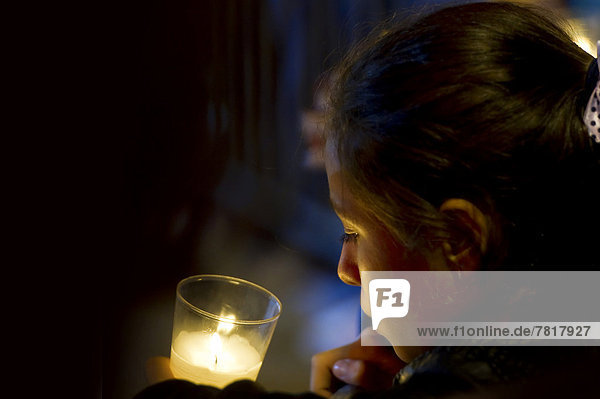 Girl with candle  in prayer