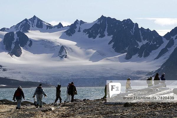 Expeditionsteilnehmer wandern bei Smeerenburg vor der Berg- und Gletscherkulisse der Vasahalvøya